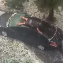Man Shields His Car from Hail With His Body, Looks Ridiculously Stupid In the Process